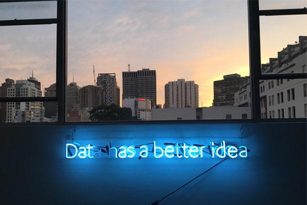 """Skyline bei untergehender Sonne aus einem Gebäude heraus fotografiert. Blauer Neonschriftzug """"Data has a better idea"""" im Vordergrund"""
