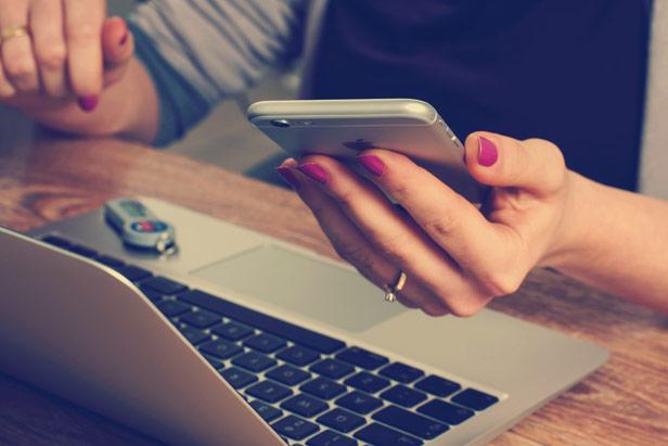 Person mit pinken Fingernägeln hält ein iPhone in der Hand und sitzt vor einem MacBook