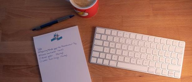handschriftliche ToDo-Liste neben weißer Tastatur, Stift und roter Kaffeetasse