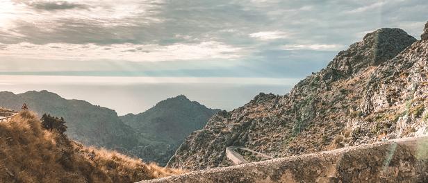 Aussicht vom Berg über die Serpentinen und die Berge in der Ferne