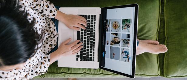Eine Frau sitzt mit ausgestreckten Beinen auf einem grünen Sofa. Sie hat ein MacBook auf dem Schoß, auf dessen Bildschirm zu erkennen ist, dass die Frau an einer Videokonferenz teilnimmt. Das Bild ist aus der Vogelperspektive aufgenommen