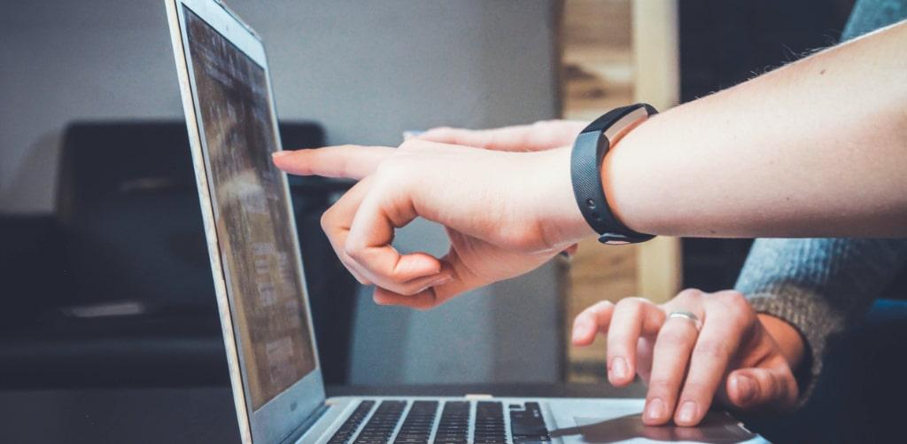 Eine Hand zeigt auf einen Laptop